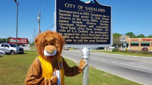 Leo, the Saraland Lions Club mascot, standing at the historical marker.